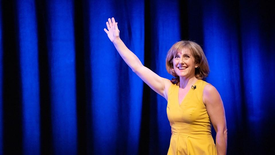 Alice Crawley waves while on stage wearing yellow dress, smiling.