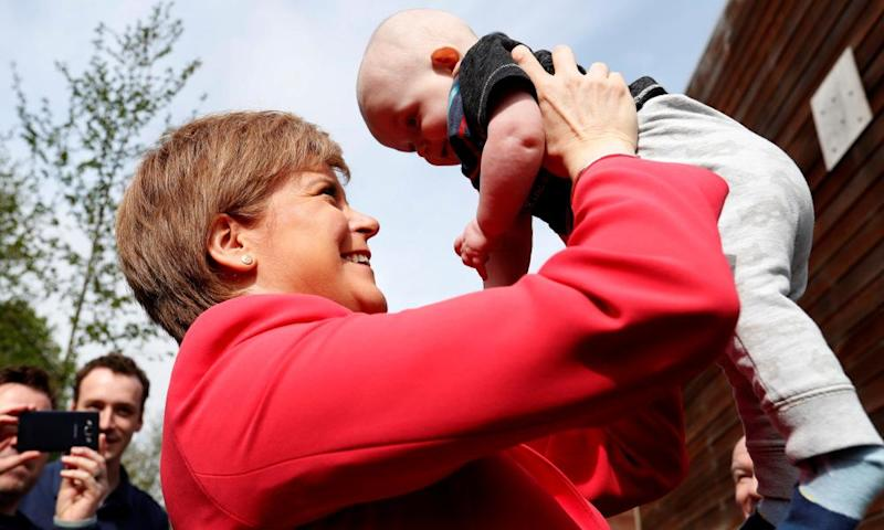 Scotland's first minister, Nicola Sturgeon, holds a baby while out campaigning in Edinburgh.