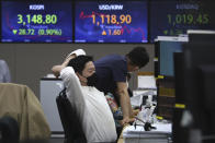 A currency trader watches monitors at the foreign exchange dealing room of the KEB Hana Bank headquarters in Seoul, South Korea, Friday, April 23, 2021. Asian stock markets were mixed Friday after Wall Street fell following a report that President Joe Biden will propose raising taxes on wealthy investors. (AP Photo/Ahn Young-joon)