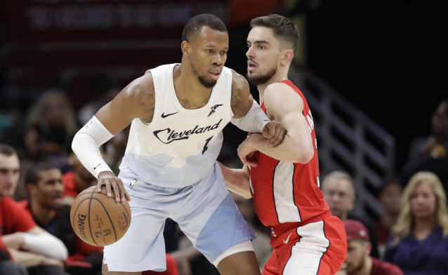 Rodney Hood, left, drives past Washington's Tomas Satoransky on Tuesday in Cleveland. (AP Photo/Tony Dejak)