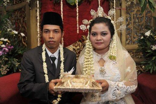 """Indonesian groom Rudiyanto (L) 26, and bride Anita Sari, 19, hold their dowry during their wedding ceremony which was held at 11 o'clock in Jakarta, on November 11. Like many other countries in the world, many people in the world's populous Muslim country flocked to registry offices to marry in the belief that the """"11/11/11"""" date is the most auspicious in a century"""