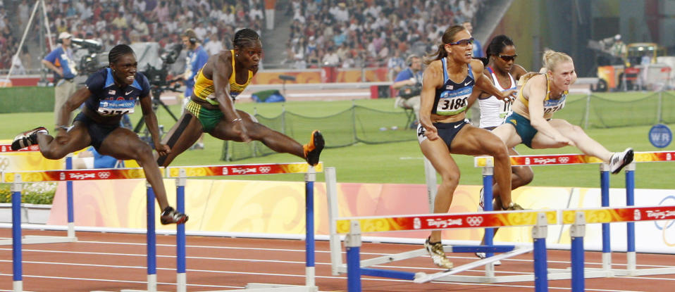"""FILE - In this Aug. 19, 2008, file photo, United States' LoLo Jones center, stumbles after hitting a hurdle in the women's 100-meter hurdles during the athletics competitions in the National Stadium at the Beijing Olympics in Beijing. When Lolo Jones opens her book, """"Over It,"""" she doesn't start with her biggest accomplishment. Instead, she opens with the """"most painful race"""" of her career—the 100-meter hurdles at the 2008 Beijing Olympics. (AP Photo/Vincent Thian, File)"""
