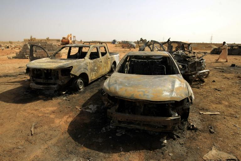 Damaged cars at the site of a bomb attack that targeted servicemen during the funeral of an ex-army commander in the Libyan city of Benghazi