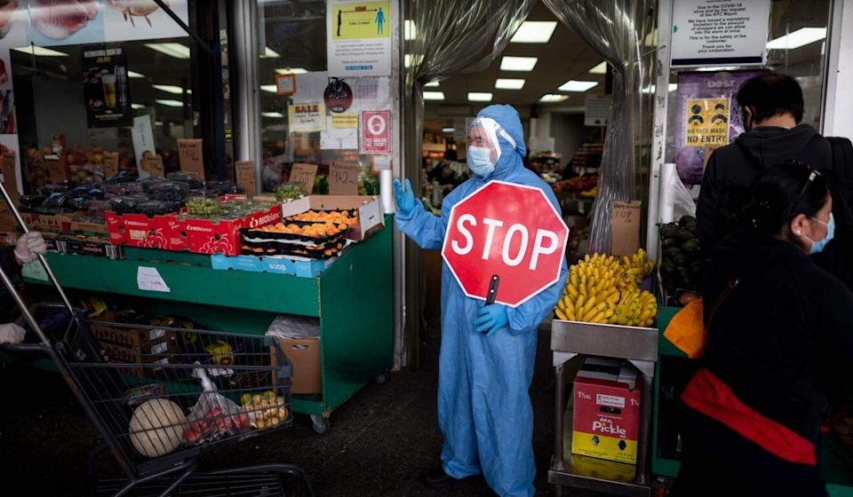 A worker wearing a full body suit holds a stop sign in front of a food market as he manages the flow of the customers on Monday in the Jackson Heights neighbourhood of Queens in New York City. Photo: AFP