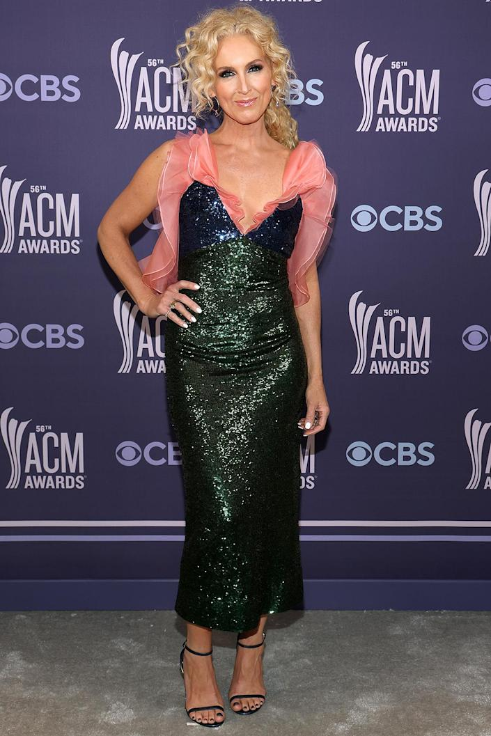 <p>in a glittery green cocktail dress with pink ruffled accents, paired with ankle-strap sandals.</p>