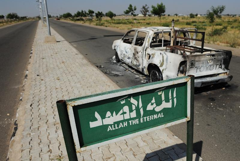A burnt police patrol pick-up truck remains abandoned on the side of a deserted road in Damaturu, in the Yobe State, on November 7, 2011
