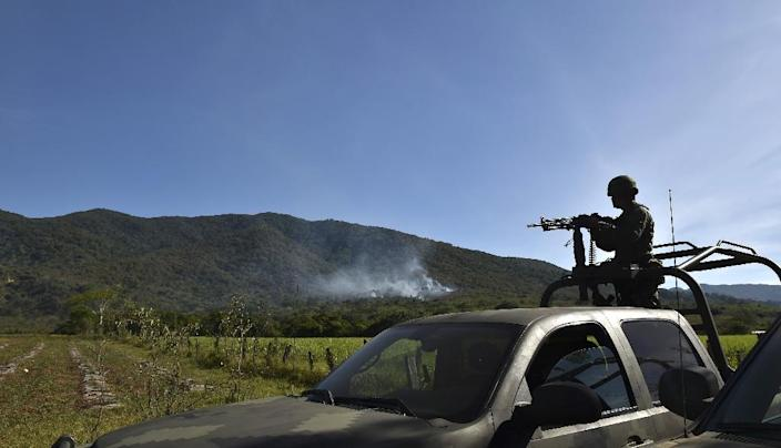 A soldier observes as smoke rises from a military helicopter that was shot down in Villa Purificacion, Jalisco State, Mexico on May 2, 2015 (AFP Photo/Yuri Cortez)