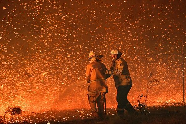 This picture taken on December 31, 2019 shows firefighters struggling against the strong wind in an effort to secure nearby houses from bushfires near the town of Nowra, NSW.