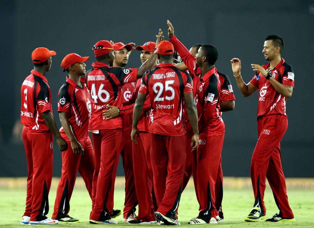 Titans and Trinidad & Tobago players celebrate fall of a wicket during the CLT20 match between Titans and Trinidad & Tobago at Sardar Patel Stadium, Motera in Ahmedabad on Sept. 30, 2013. (Photo: IANS)
