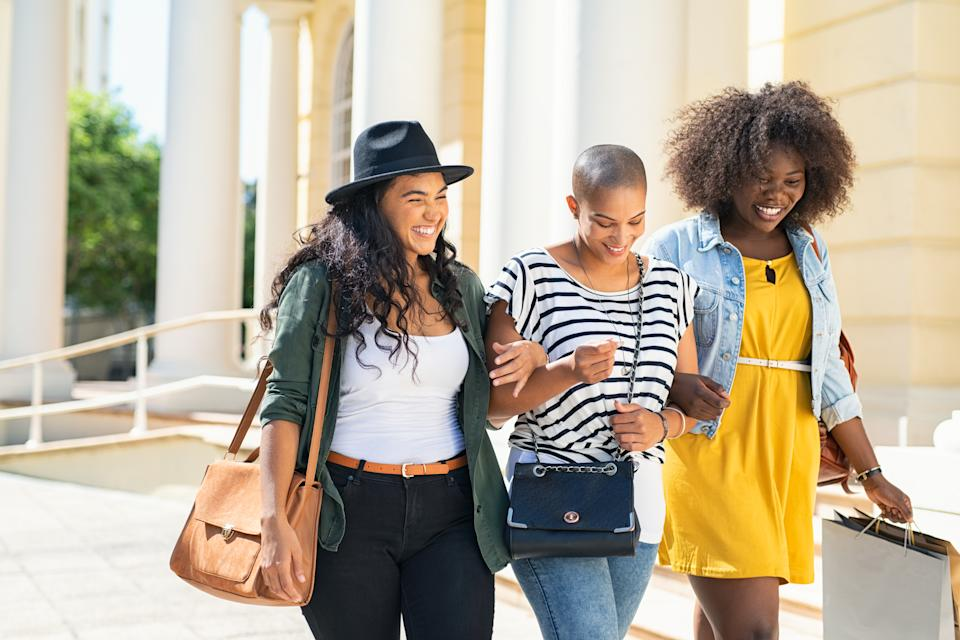 Group of three friends walking and holding shopping bags. Three happy young women walking in the city talking to each other while having fun on street. Multiethnic group of girls smiling with shopping bags outdoor.
