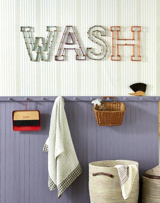 """<p>Gussy up the laundry room or a kids' bath with appropriate words like """"wash"""" or """"splash."""" Start by cutting out letters from craft paper. Mark nail holes with a pencil on the wall using the letters as a guide. Hammer copper nails into the wall, and wrap nails with lengths of assorted-colored thick yarn. </p>"""