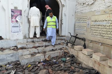 A rescue worker steps outside where victims' shoes are scattered after an explosion in a Shi'ite mosque in Shikarpur, located in Pakistan's Sindh province January 30, 2015. REUTERS/Amir Hussain