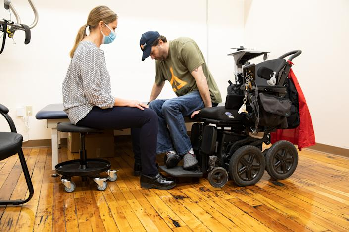 Dawn Hamline, clinical educator, watches as Derek O'Brien, an iBOT personal mobility device user, gets into his iBOT at Mobius Mobility headquarters, on May 4, 2021, in Manchester, New Hampshire. (Kayana Szymczak for Yahoo News)