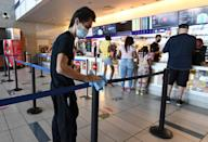 <p>An employee sanitizes stanchions at the concession stand at AMC Town Square 18 on August 20 in Las Vegas, Nevada. </p>