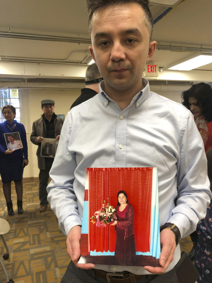 FILE - In this file photo taken Sunday, Feb. 24, 2019, Ferkat Jawdat holds up a photo of his mother during a gathering to raise awareness about loved ones who have disappeared in China's far west Xinjiang region in Washington DC. The accusation of genocide by U.S. Secretary of State Mike Pompeo against China touches on a hot-button human rights issue between China and the West. (AP Photo/Christina Larson, File)
