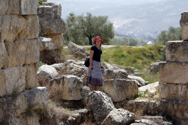 In this Saturday, April 6, 2013 photo, an Italian tourist visits the Roman Temple of Augustus in the village of Sebastia near the West Bank city of Nablus. The ancient town of Sebastia is one of the greatest archaeological sites of the Holy Land, attracting tourists and pilgrims over the centuries with its overlapping layers of history dating back 3,000 years. But visitors who come to the site today will find it in a state of neglect. (AP Photo/Majdi Mohammed)
