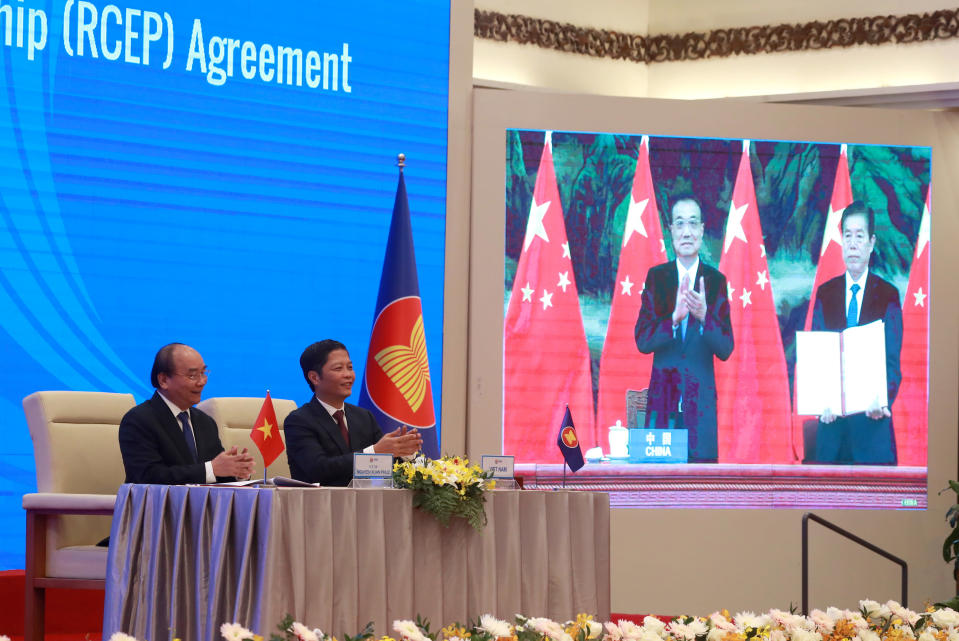 Vietnamese Prime Minister Nguyen Xuan Phuc, left, and Minister of Trade Tran Tuan Anh, right, applaud next to a screen showing Chinese Premier Li Keqiang and Minister of Commerce Zhong Shan holding up signed RCEP agreement, in Hanoi, Veitnam. China and 14 other countries have agreed to set up the world's largest trading bloc, encompassing nearly a third of all economic activity, in a deal many in Asia are hoping will help hasten a recovery from the shocks of the pandemic. (AP Photo/Hau Dinh)