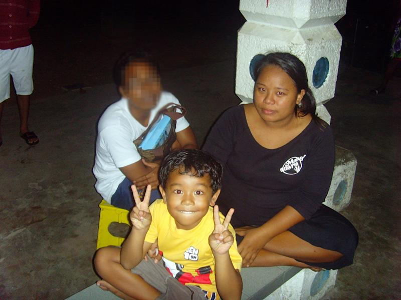 Liyana and one of sons in 2009 when camping at Sembawang Park. Her then-husband's identity has been obscured upon her request. (PHOTO: Ravi Philemon)