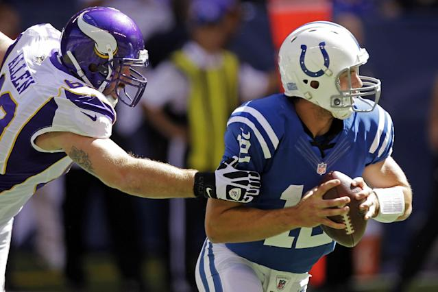 Indianapolis Colts quarterback Andrew Luck, right, runs out of the grasp of Minnesota Vikings' Jared Allen during the first half of an NFL football game in Indianapolis, Sunday, Sept. 16, 2012. (AP Photo/Michael Conroy)