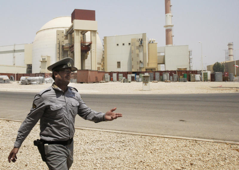 FILE - In this Saturday, Aug. 21, 2010, file photo, an Iranian security directs media at the Bushehr nuclear power plant, with the reactor building seen in the background, just outside the southern city of Bushehr, Iran. The U.S. has plans in place to attack Iran if necessary to prevent it from developing nuclear weapons, Washington's envoy to Israel said, days ahead of a crucial round of nuclear talks with Tehran. (AP Photo/Vahid Salemi, File)