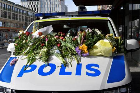 People leaving flowers on a police van outside Ahlens department store following Friday's terror attack in central Stockholm, Sweden, Sunday, April 9, 2017. Jonas Ekstromer/TT News Agency via REUTERS