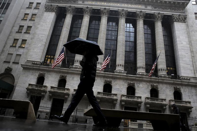 A man passes by the New York Stock Exchange during a rain storm in New York