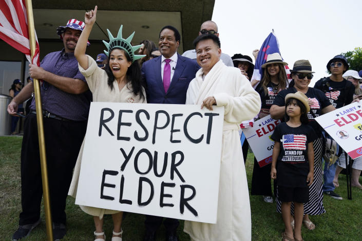 FILE — In this July 13, 2021 file photo radio talk show host Larry Elder poses for pictures with supporters during a campaign stop in Norwalk, Calif. Alexandra Datig, Elder's former fiancee said Thursday, Aug. 19 that Elder once displayed a gun to her during a heated argument in 2015. Elder said he never brandished a gun at anyone. AP Photo/Marcio Jose Sanchez, File)