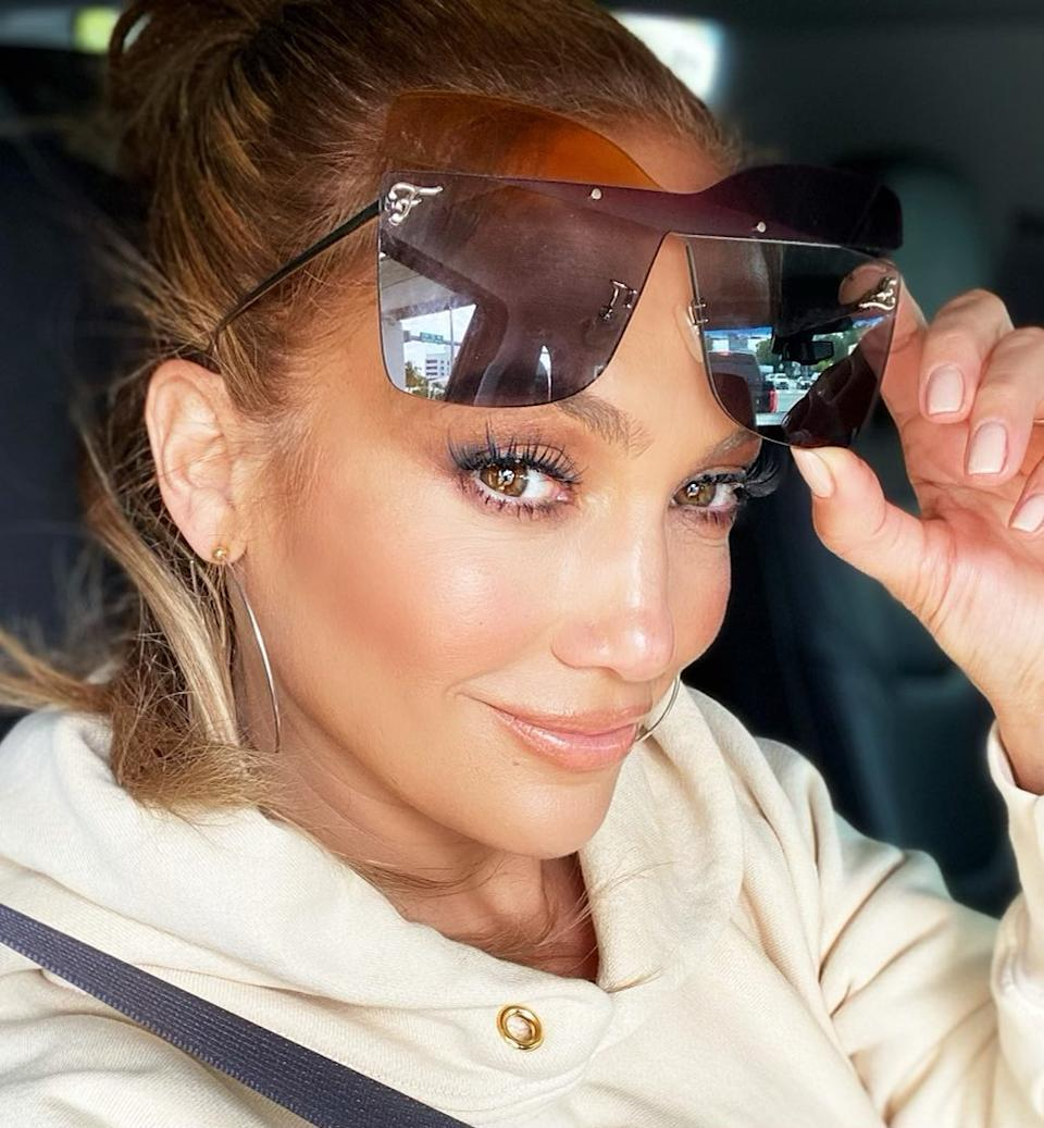 JLo in the car pulling up her sunglasses