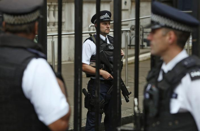 Armed police officers are seen on duty in Downing Street, central London September 1, 2014. British Prime Minister David Cameron said on Monday he would bring in new laws to give police the power to seize the passports of suspected Iraq and Syria-bound Islamist fighters. REUTERS/Luke MacGregor (BRITAIN - Tags: POLITICS CONFLICT CRIME LAW)