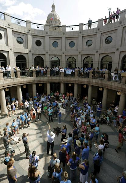 A man blows a horn as supporters and opponents of an abortion bill gather in a near a hearing for the bill at the state capitol, Tuesday, July 2, 2013, in Austin, Texas. Gov. Rick Perry has called lawmakers back for another special session with abortion on the top of the agenda. (AP Photo/Eric Gay)
