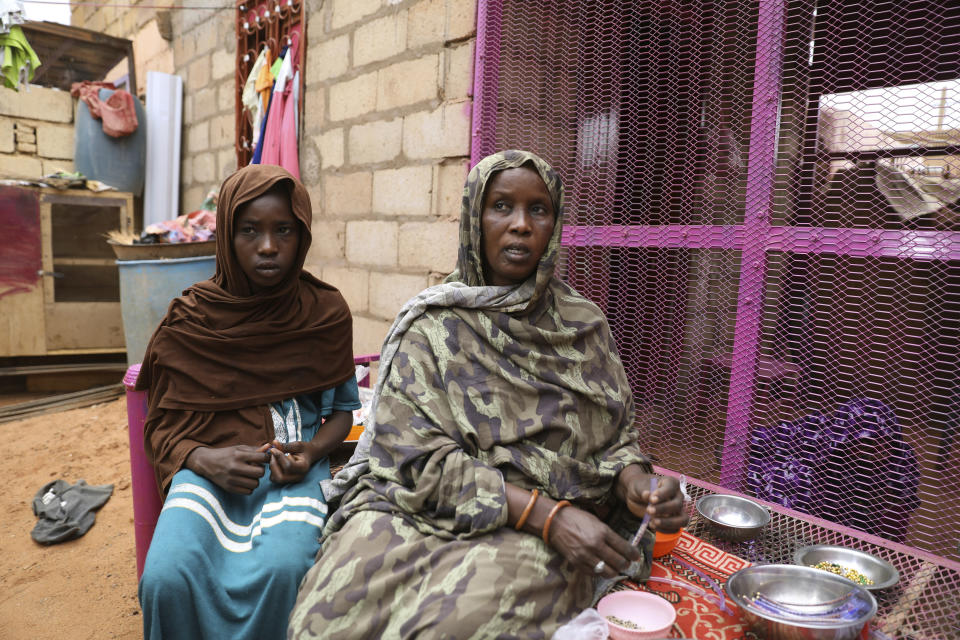 Saadia Ahmed, mother of the Sudanese migrant Mutawakel Ali, sits with her daughter at her home, in Khartoum, Sudan, Friday April 30, 2021. Ali narrowly missed drowning in Libya because he was late for the boat's departure. The rubber boat when on to sink at sea on approximately April 21, and its more than 100 passengers drowned. (AP Photo/Marwan Ali)