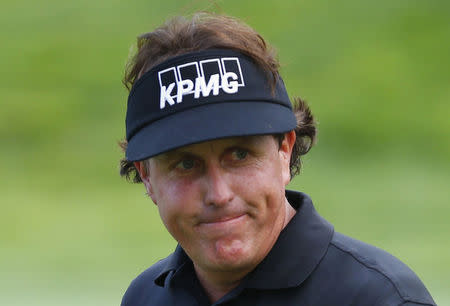 Phil Mickelson of the U.S. reacts after his birdie on the 11th hole during the first round of the 2013 PGA Championship golf tournament at Oak Hill Country Club in Rochester, New York in this August 8, 2013 file photo. REUTERS/Jeff Haynes/Files