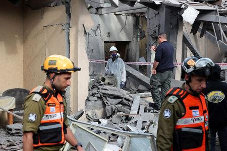 Israeli policemen and soldiers inspect a damaged house that was hit by a rocket north of Tel Aviv Israel March 25, 2019. REUTERS/ Ammar Awad