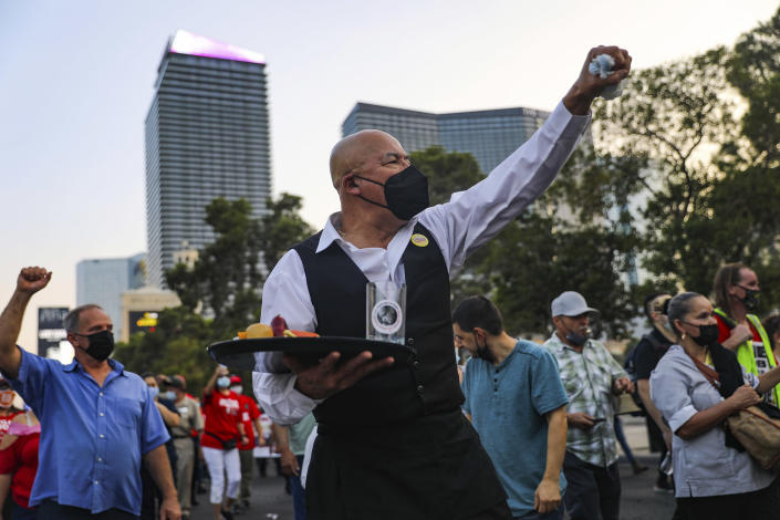 Jose Rivera, center, chants with other members of the Culinary Workers Union to bring attention to the 21,000 members who are still not back to work since the pandemic began, during a march, Friday, Sept. 24, 2021 on the Strip in Las Vegas. (Rachel Aston/Las Vegas Review-Journal via AP)