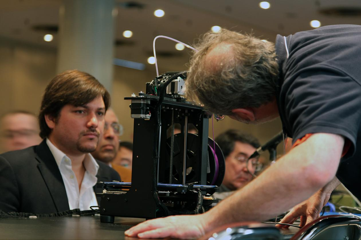 A presenter at the conference tinkering with a desktop 3D printer during one of the breakout sessions. Different models of 3D printers were printing side by side to demonstrate to their commonalities and differences.