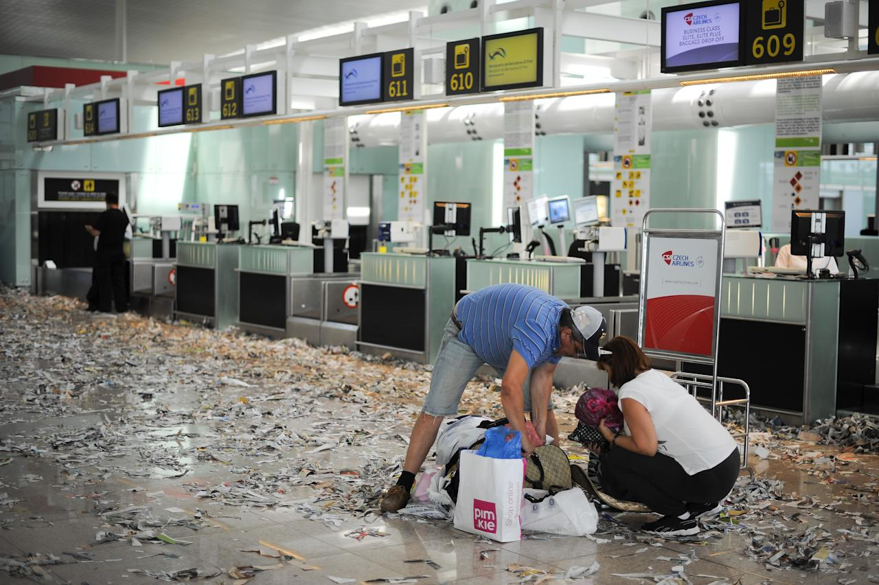 BARCELONA, SPAIN - MAY 29:  Passangers check theis luggage among rubbish and papers as Barcelona Airport cleaning staff protest against budget cuts at the El Prat International Airport on May 29, 2012 in Barcelona, Spain. Barcelona Airport cleaning staff are holding a two days strike portesting against the 1.3 million Euros budget cut that the airport operator company AENA has announced.  (Photo by David Ramos/Getty Images)