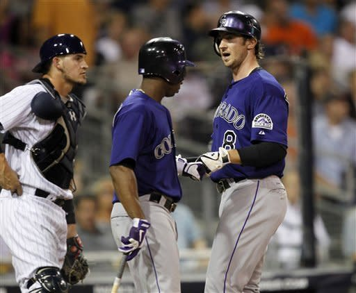 Colorado Rockies' Charlie Blackmon, right, gets congratulations from Jonathan Herrera, center, after hitting a solo home run as San Diego Padres catcher Yasmani Grandal, left, looks away during the first inning of their baseball game in San Diego, Calif., Friday, Sept. 14, 2012. (AP Photo/Alex Gallardo)