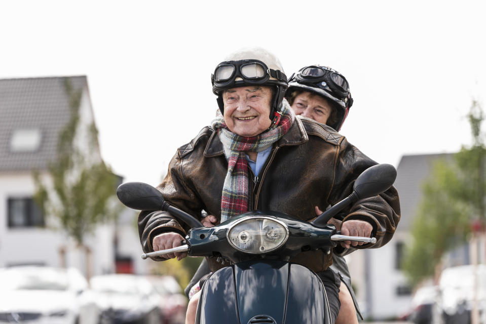 Happy senior couple riding motor scooter. Photo: Getty Images