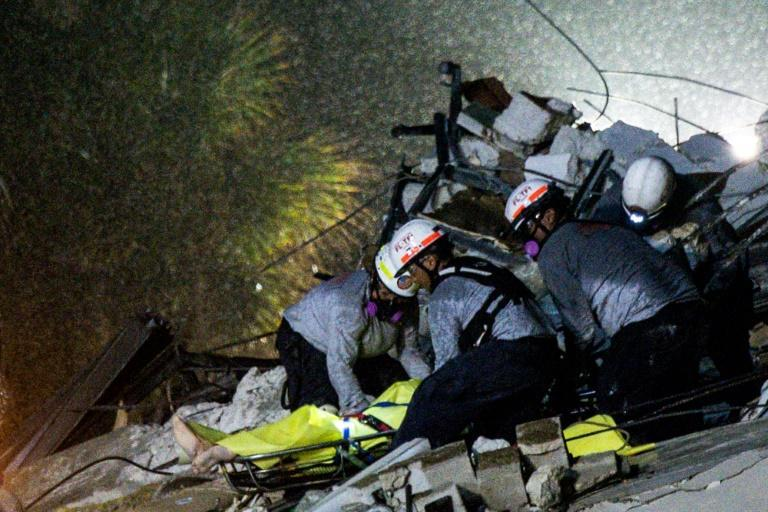 Search and rescue personnel pull a body out of the rubble after the partial collapse of the Champlain Towers South in Surfside, north of Miami Beach