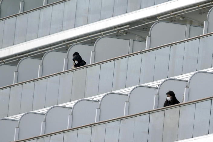 Masked passengers stand outside on the balcony of the ship (AP)