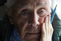 """Artist Robert Seaman poses in his room at an assisted living facility Monday, May 10, 2021, in Westmoreland, N.H. Seaman, who moved into the facility weeks before the COVID-19 pandemic shutdown his outside world in 2020, recently completed his 365th daily sketch, or what he calls his """"Covid Doodles"""", since being isolated due to the virus outbreak. (AP Photo/Charles Krupa)"""