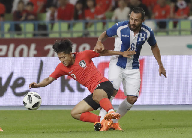 South Korea's Lee Seung-woo, left, fights for the ball against Honduras' Alfredo Mejia during their friendly soccer match in Daegu, South Korea, Monday, May 28, 2018. (AP Photo/Lee Jin-man)