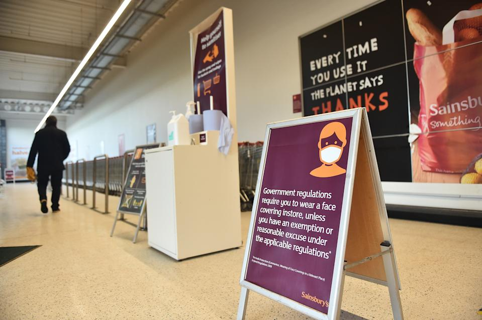 NEWCASTLE-UNDER-LYME, ENGLAND - JANUARY 12: A man walks past a face covering sign while shopping in Sainsburys on January 12, 2021 in Newcastle-Under-Lyme, England. In response to government ministers voicing concerns about the public's behaviour in supermarkets, Sainsbury's and Morrisons have both announced they will be enforcing rules on mask-wearing in their stores. The daily admissions to hospitals of coronavirus cases  has topped 4000 and the current number of patients in hospital with the virus is 32,294. (Photo by Nathan Stirk/Getty Images)