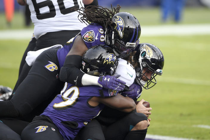 Jacksonville Jaguars quarterback Gardner Minshew II, right, is sacked for a safety by Baltimore Ravens linebacker Pernell McPhee (90) and linebacker Matthew Judon (99) during the first half of an NFL football game, Sunday, Dec. 20, 2020, in Baltimore. (AP Photo/Nick Wass)