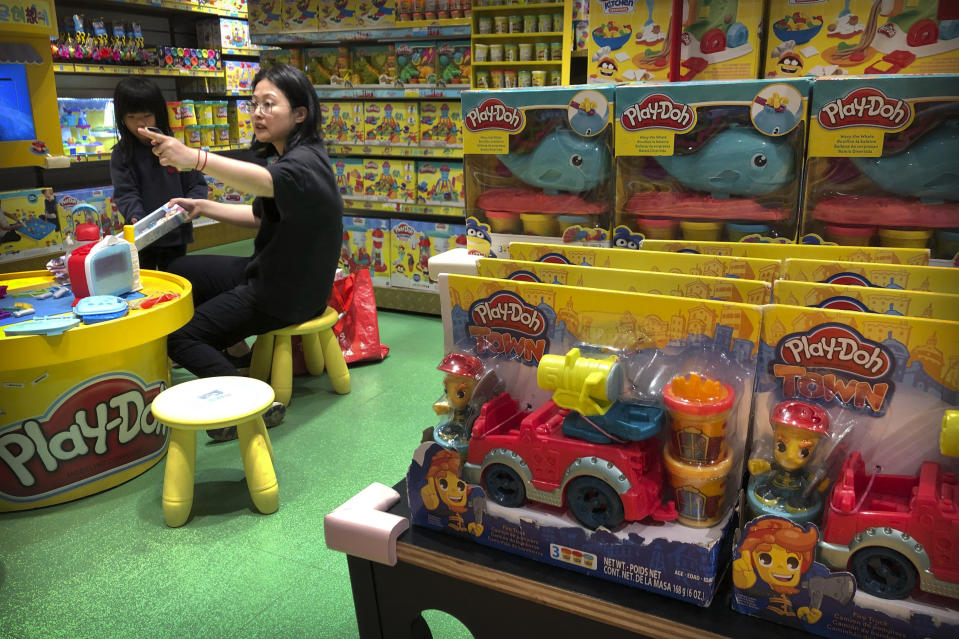 A woman and child play at a display for Play-Doh toys made by American toymaker Hasbro at a toy store in Beijing, Wednesday, May 15, 2019. For many Americans, President Donald Trump's trade war may soon get very real. His administration is preparing to extend 25% tariffs to practically all Chinese imports not already hit with duties, including toys, sneakers, shirts, alarm clocks, toasters and coffeemakers. (AP Photo/Mark Schiefelbein)