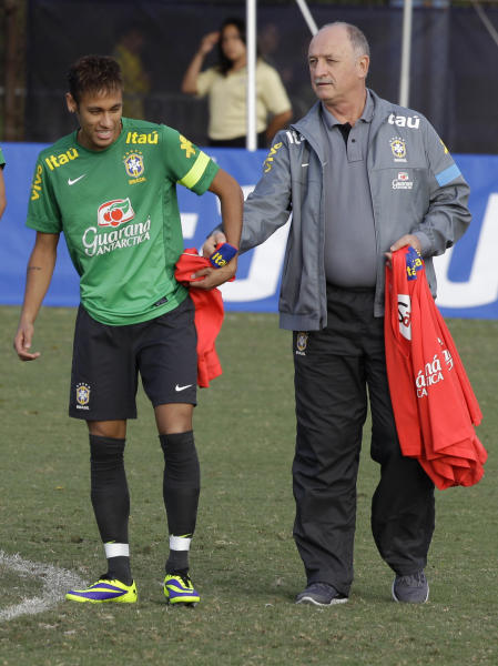 Brazil head coach Luis Felipe Scolari, right, gives a T-shirt to Neymar during a practice session in Miami, Thursday, Nov. 14, 2013. Brazil is to face Honduras in an international friendly soccer match on Saturday. (AP Photo/Javier Galeano)