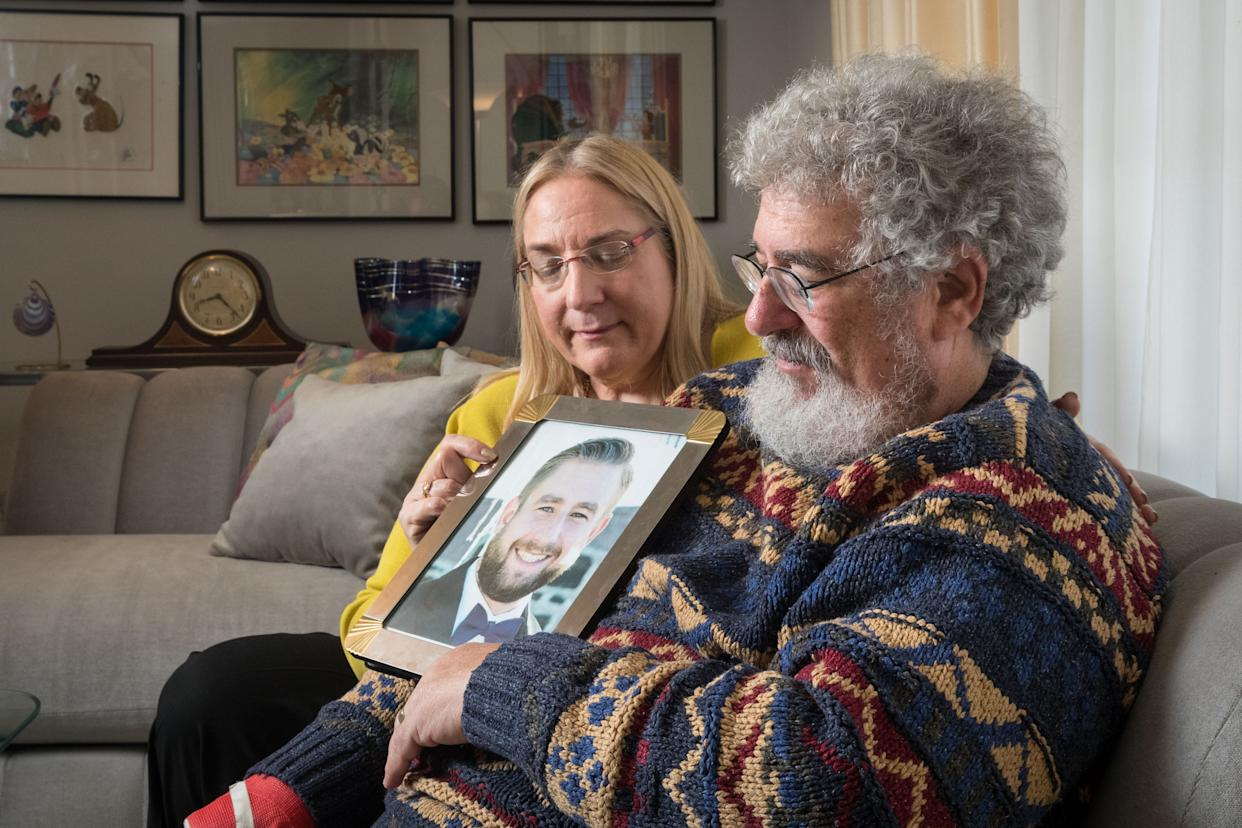 Mary Rich and her husband, Joel Rich, with a photo of their son Seth. (Photo: Matt Miller for the Washington Post via Getty Images)