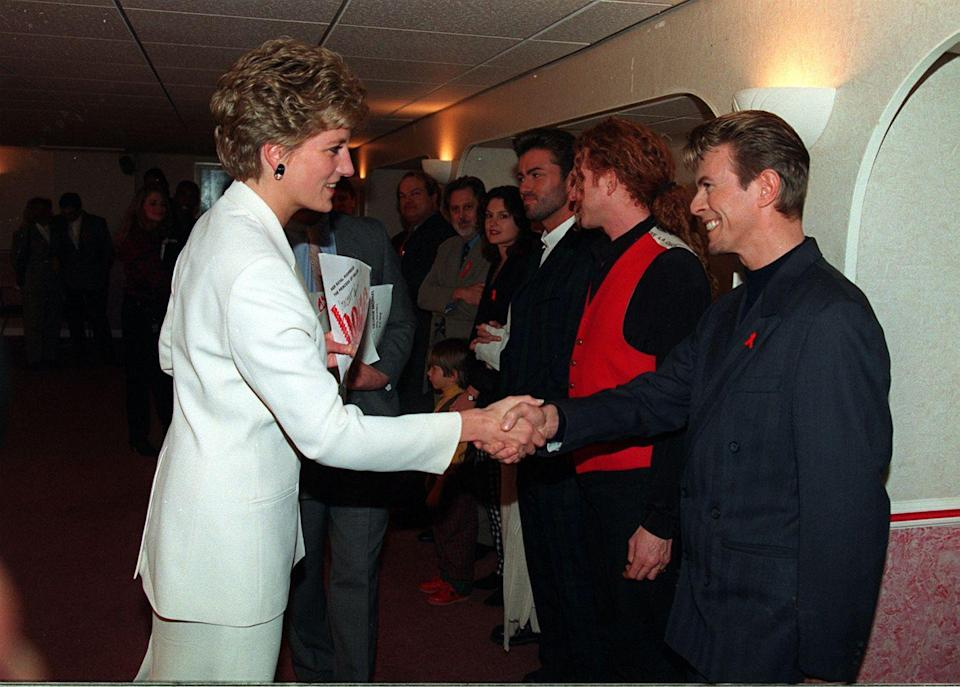 <p>Ahead of the singer's performance at a concert for World AIDS Day in 1993, he met Princess Diana and wore a remarkably tame black suit paired with his AIDS awareness red ribbon. </p>