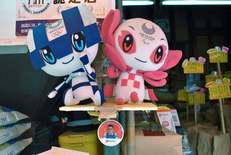 Tokyo 2020 mascots and PayPay app sticker are displayed at rice dealer's shop in Tokyo