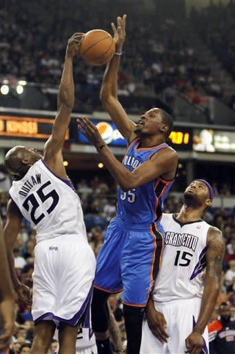 Oklahoma City Thunder forward Kevin Durant, center, has his shot blocked by Sacramento Kings forward Travis Outlaw (25) but was fouled on the play by Kings center DeMarcus Cousins (15) during the first quarter of an NBA basketball game in Sacramento, Calif., Friday, April 20, 2012. (AP Photo/Rich Pedroncelli)
